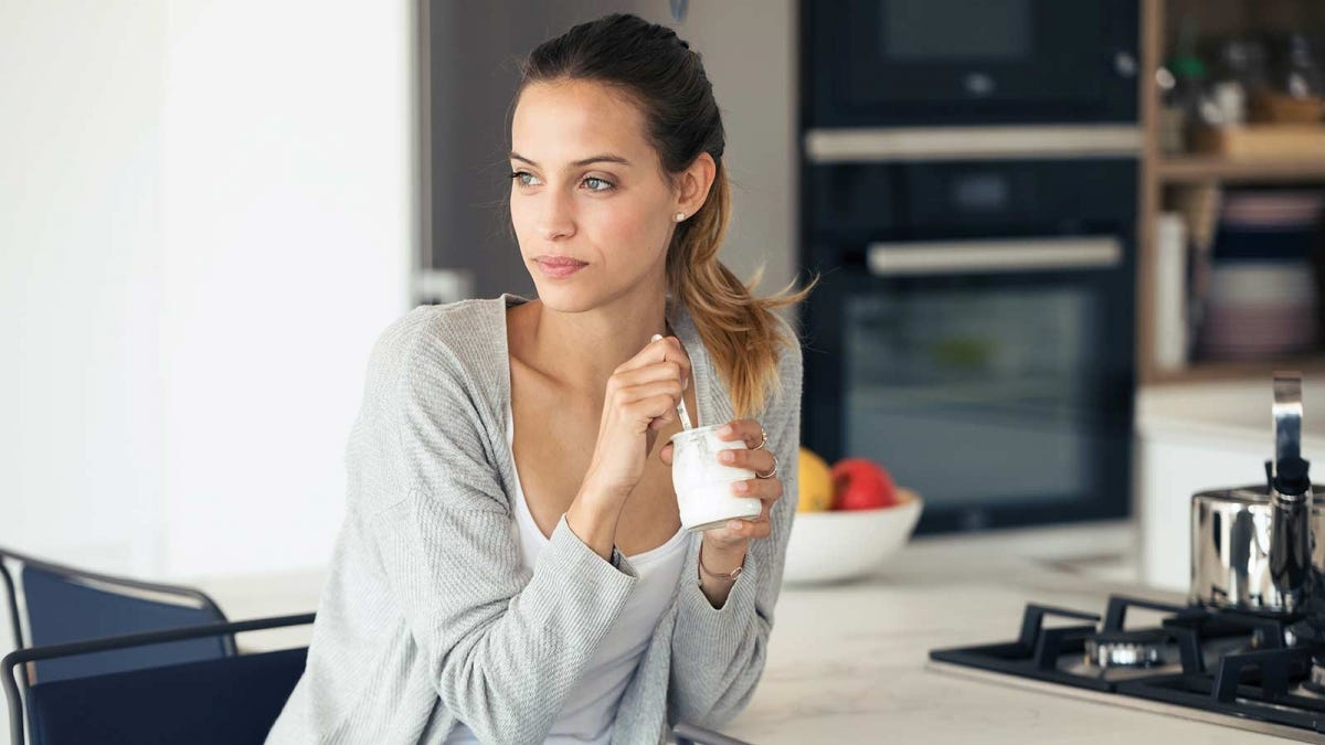 A woman holding a yogurt container and spoon.