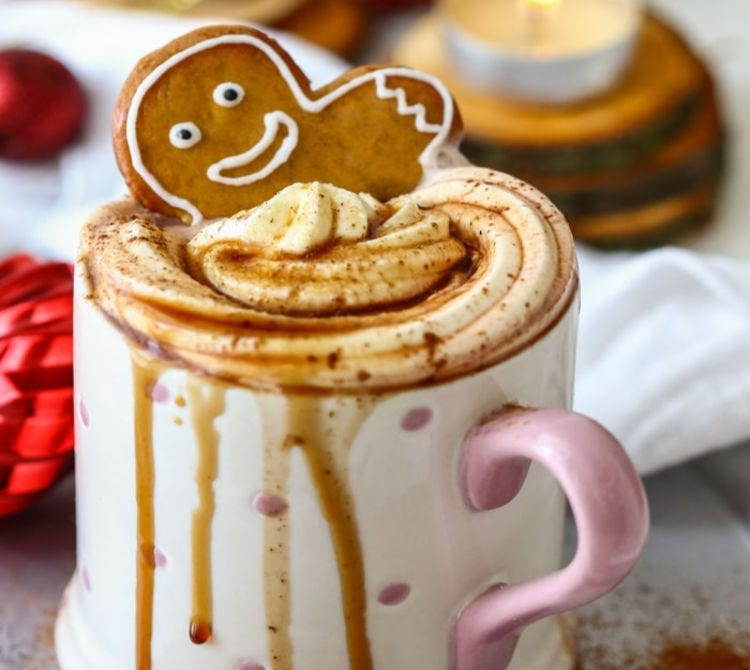 A white and pink mug filled with gingerbread hot coco, garnished with whipped cream and a gingerbread man cookie. The sticky mug is overflowing with hot chocolate, and dripping alongside the mug.