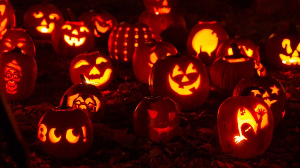 An assortment of carved pumpkins with fancy designs.