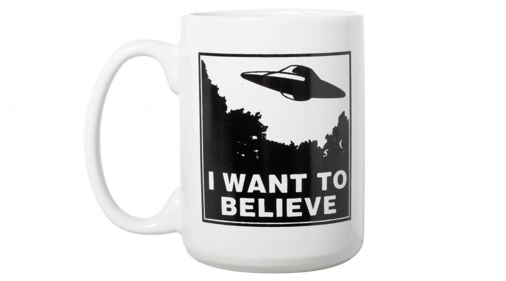 """""""I Want to Believe"""" on a mug with an image of a flying saucer on it."""