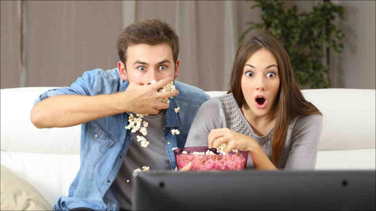 Amazed couple watching movie sitting on a couch at home