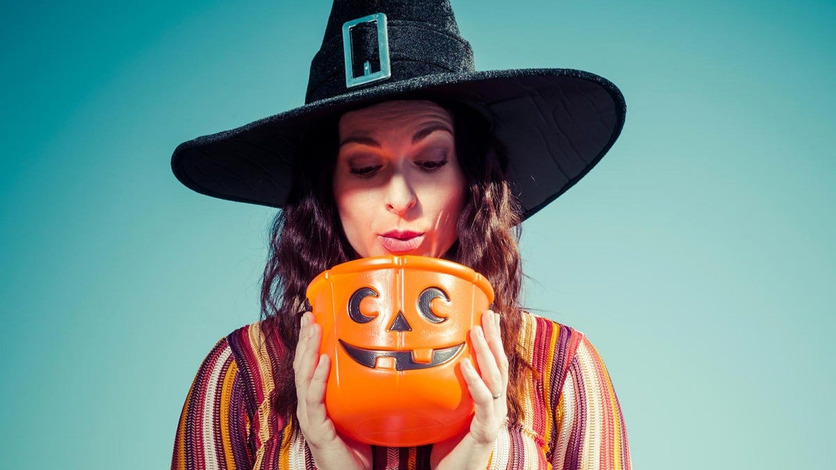 woman with a witch hat on looking into a jack o' lantern pumpkin bowl