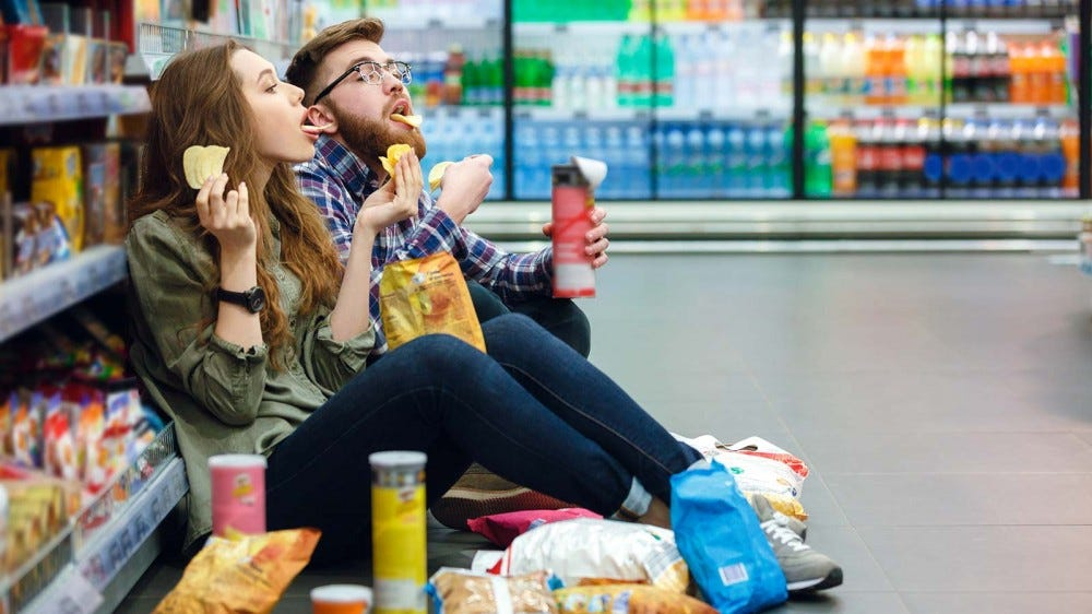 A couple sitting on the floor of a gas station eating junk food.