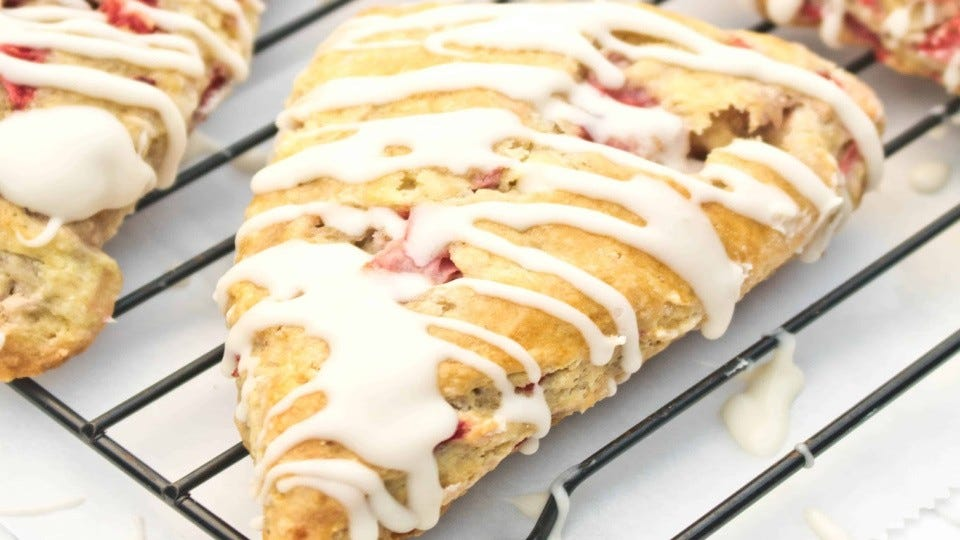Two strawberry scones on a cooling rack, with a creme glaze drizzled on top.