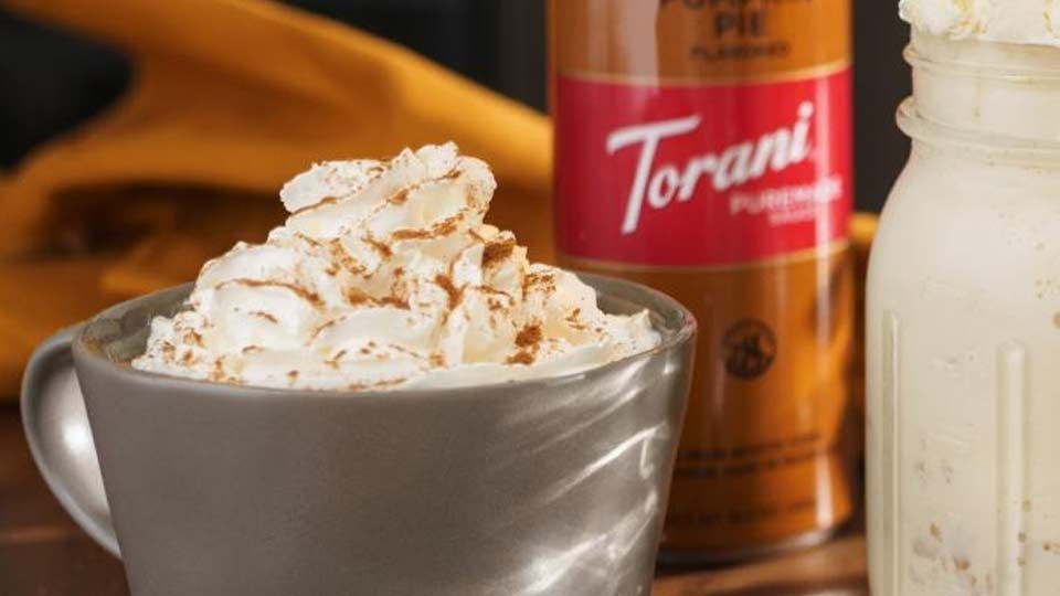 Torani pumpkin flavored sauce, sitting next to a pumpkins spice latte.