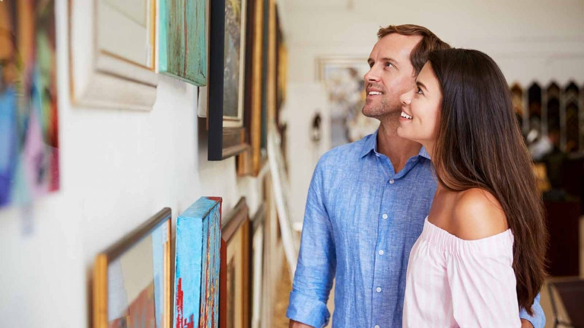 Couple looking at artwork in a gallery.