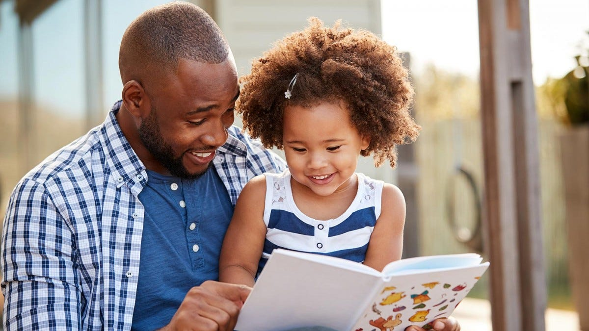 A man with a little girl on his lap looking at a book.