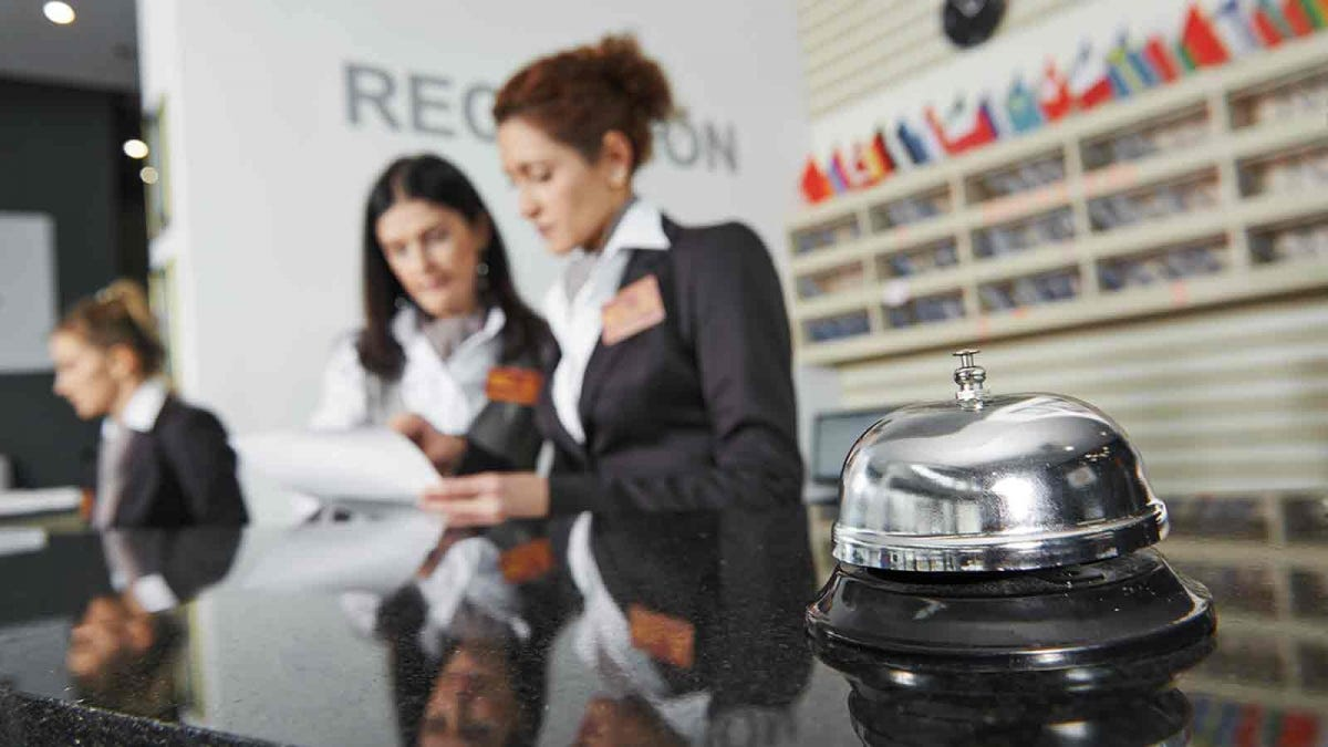reception desk at a large international hotel with a shiny service bell on the counter