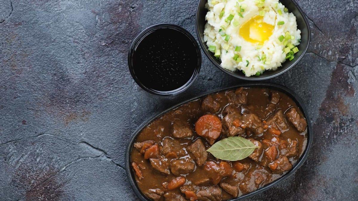 A pint of dark beer, Irish-style potatoes, and an Irish stew.