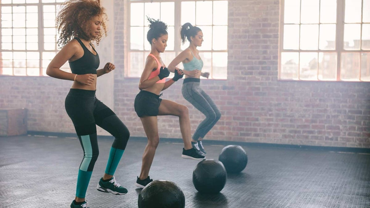 woman taking a boot camp style aerobics class and exercising with medicine balls