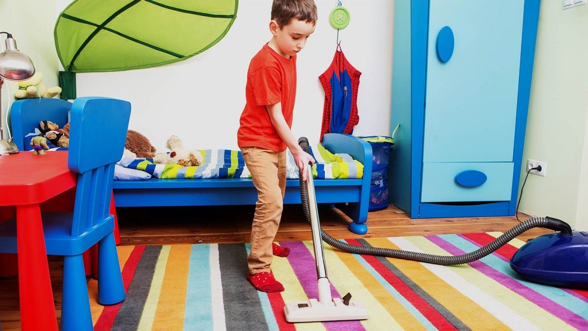 A young boy vacuuming his room.