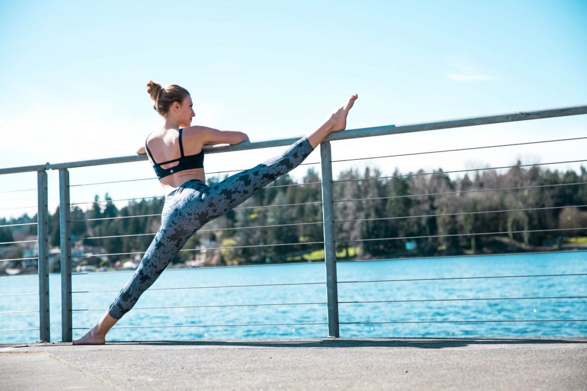 A woman stretching her leg on a railing by water.