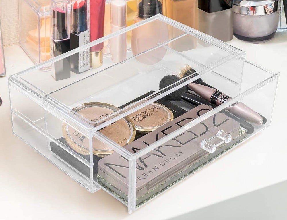 Clear rectangular drawer on a counter, with makeup products inside