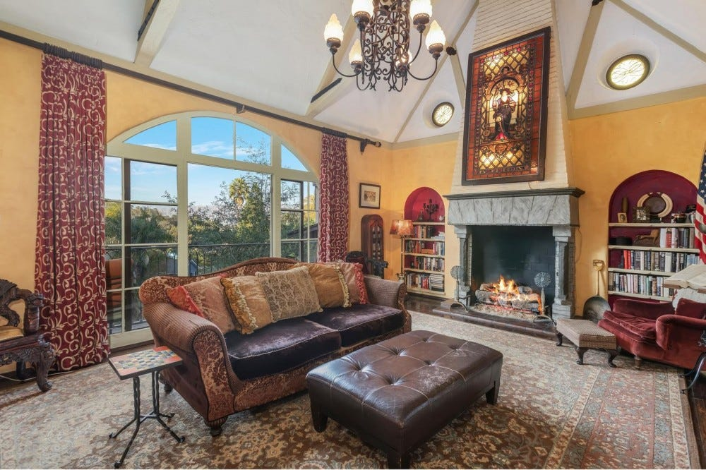 A living room featuring medieval accents, like a grand stained glass piece of art, leather furniture, a fireplace, and an arched window.