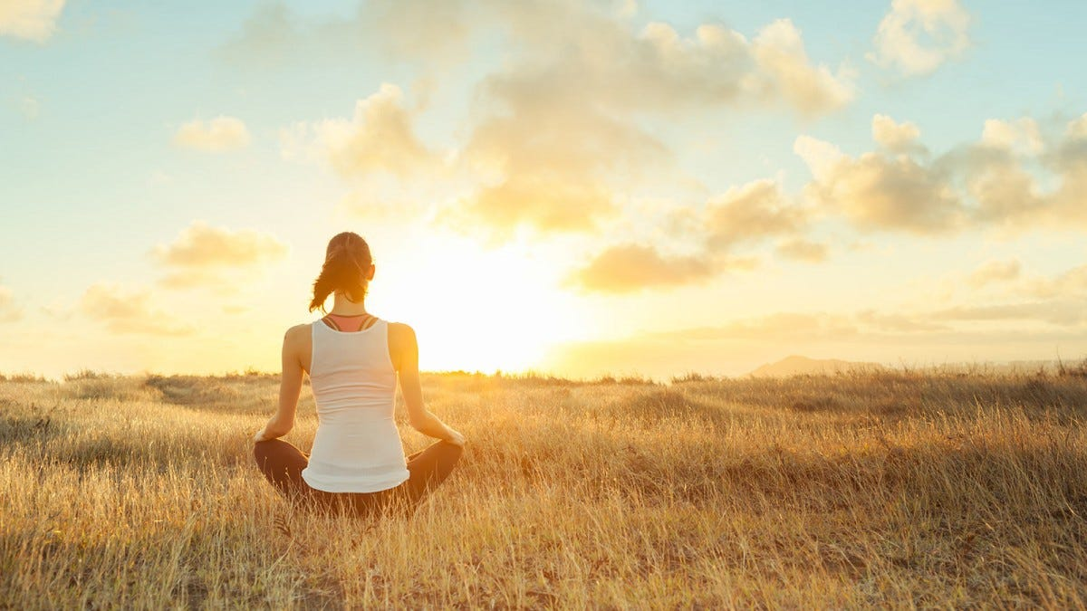 Woman meditating in a field at sunset.