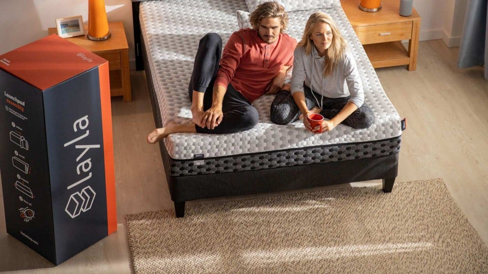 A couple is sitting on a newly unpacked Layla mattress.