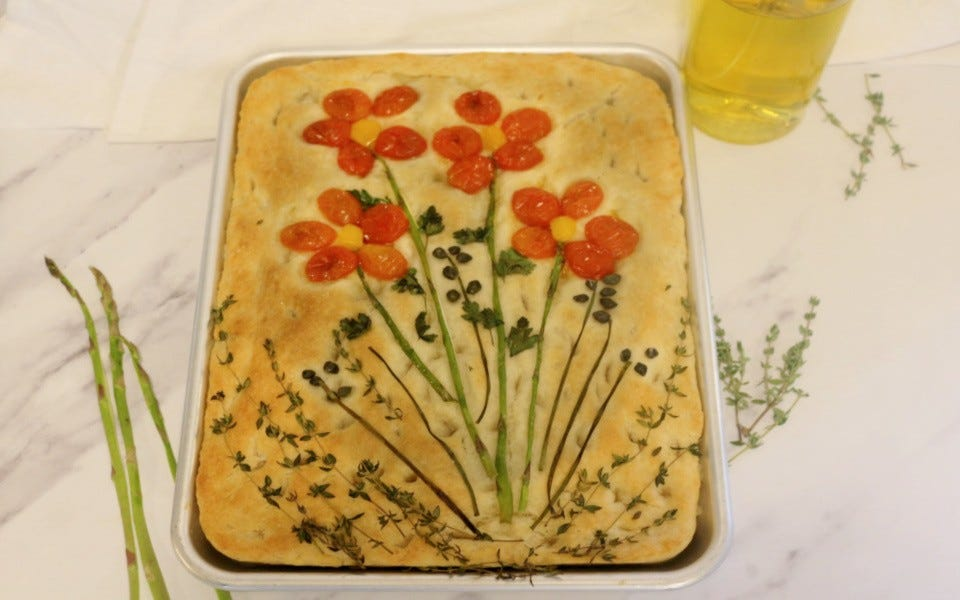 A baked, golden brown focaccia bread fresh with a bouquet of veggie and herb flowers on top.