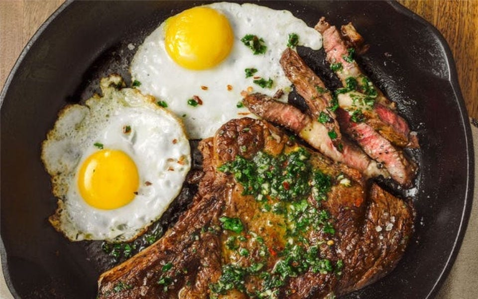 A seared bone-in rib eye steak, topped with fresh chimichurri sauce, with a side of two sunny-side-up eggs.