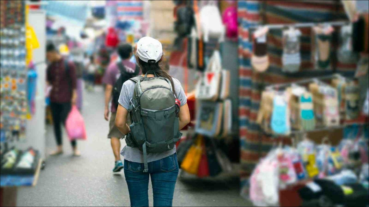 Female traveler with backpack walking market street
