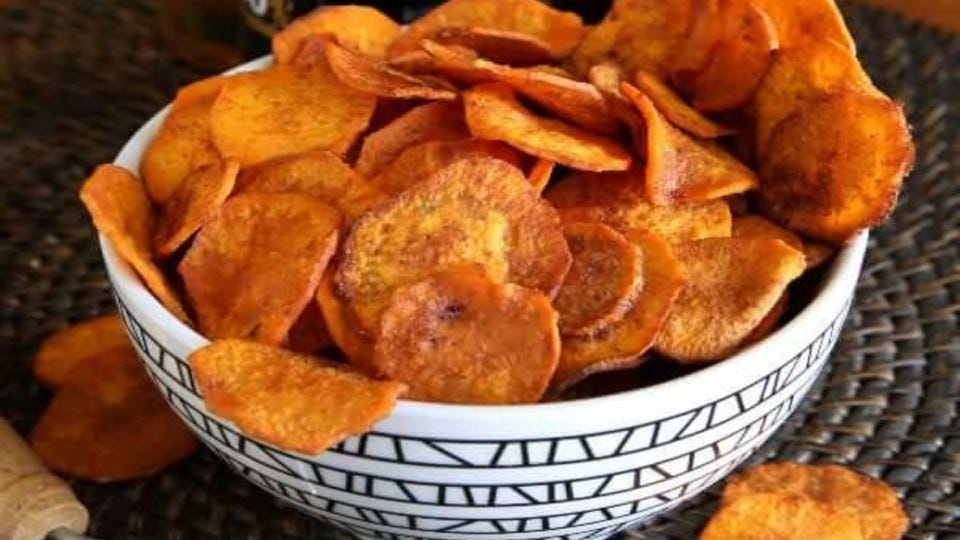 A heaping bowl of freshly air-fried sweet potato chips coated with a spicy seasoning blend.