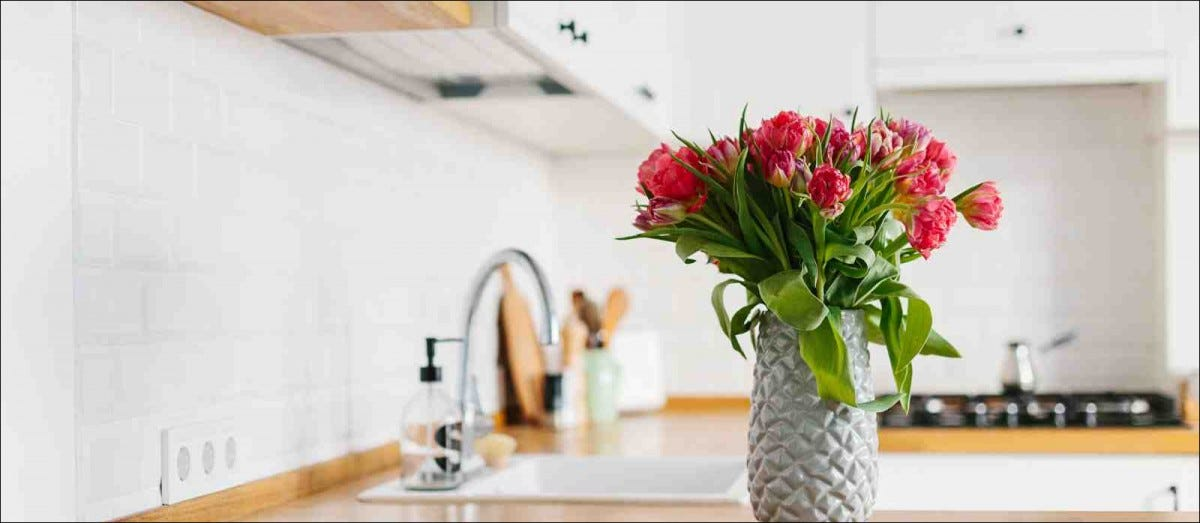 Tulips bouquet in vase standing on wooden countertop in the kitchen
