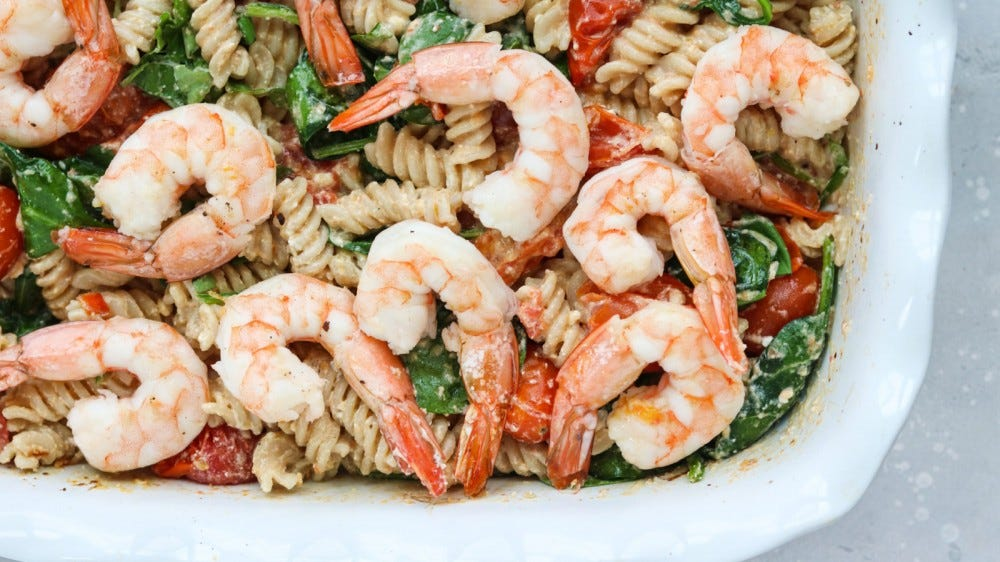 A platter of baked feta pasta topped with shrimp.
