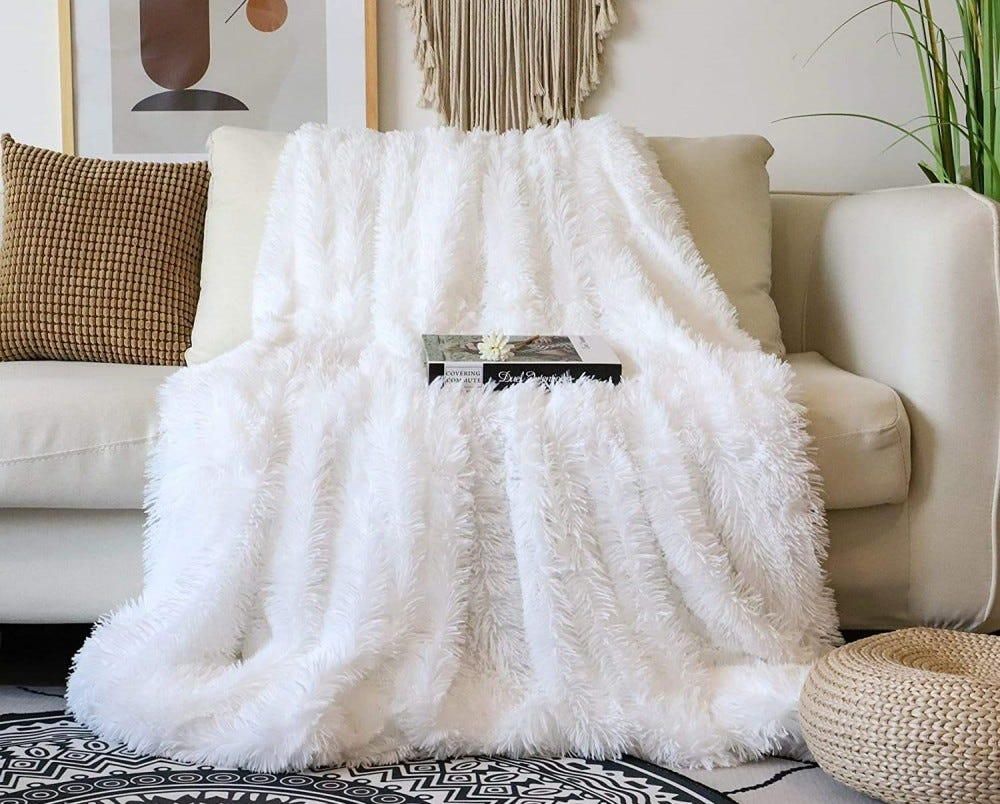 A fluffy white blanket draped over a sofa with a book on top of it.