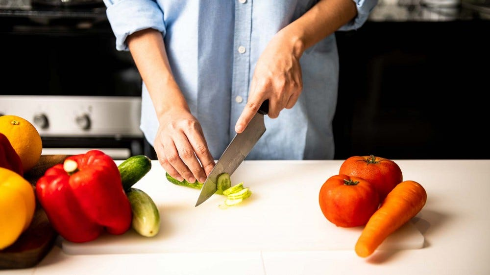 A woman cutting vegetables with a high quality chef's knife.