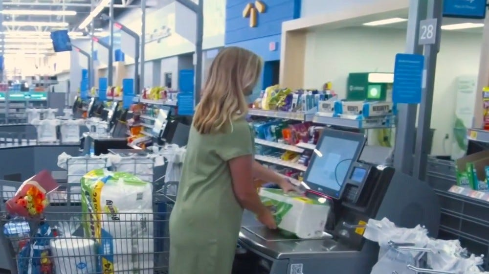 A woman sliding an item over the scanner at a self-checkout in a Walmart.