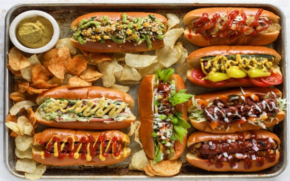 Eight hot dogs embellished with different topping combinations, surrounded by chips and a side of mustard.