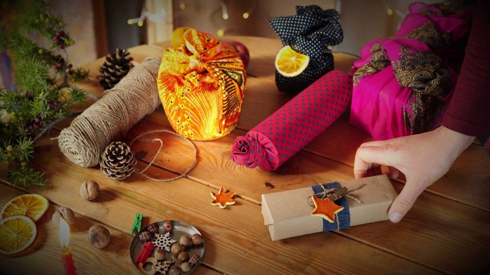 A table covered in gifts wrapped in alternatives to traditional gift wrap, like craft paper or cloth.