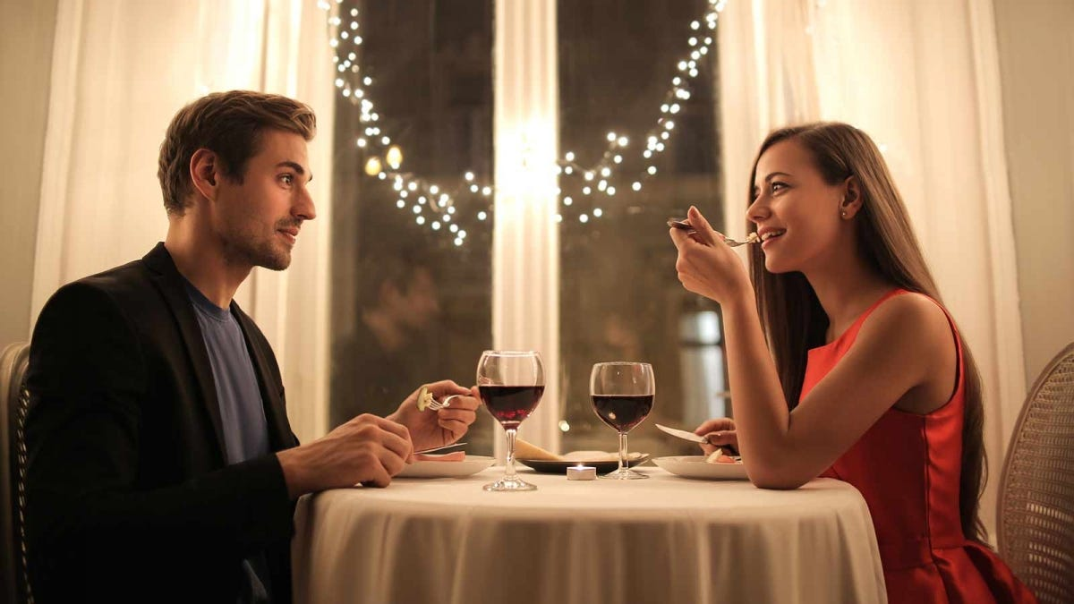 A couple having a romantic at-home dinner, capturing the restaurant-experience.