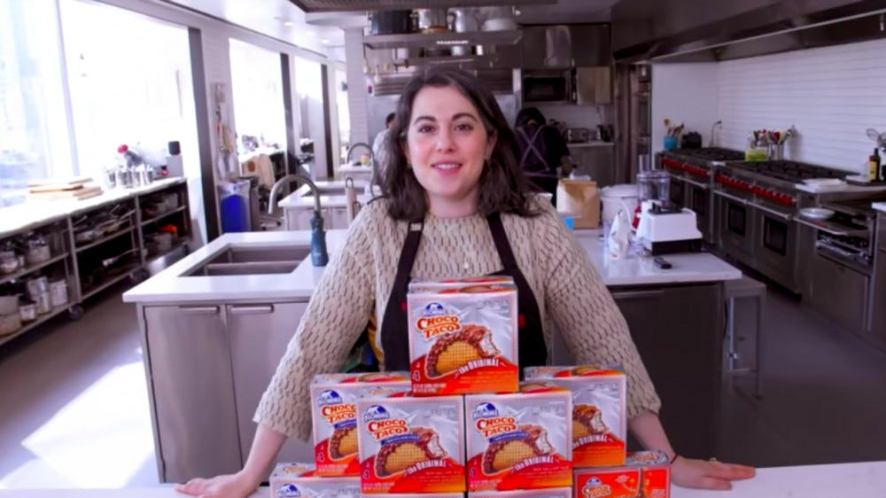 Gourmet Chef, Claire Saffitz, standing behind a stack of Klondike Choco Taco packages on a counter.