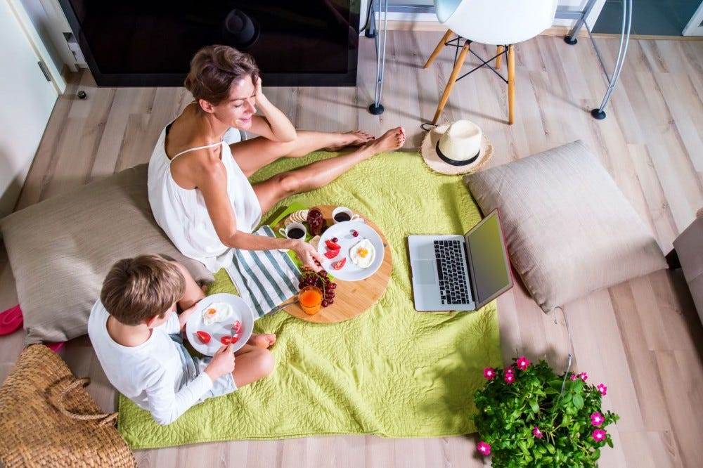 A mom and son having an indoor picnic on the floor.