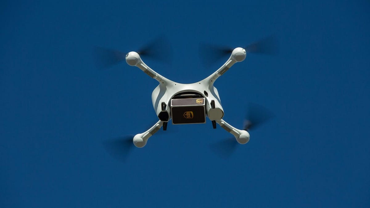 A UPS delivery drone flying a UPS package filled with medication to a drop off zone.