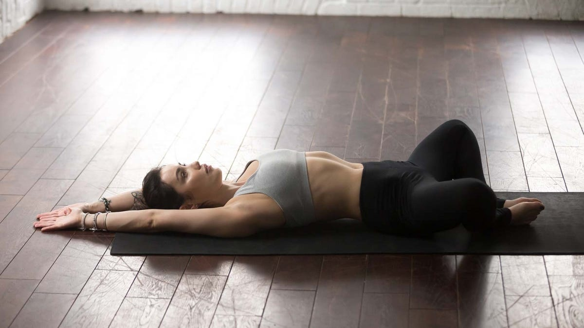 woman performing a reclined butterfly pose to open up her hips