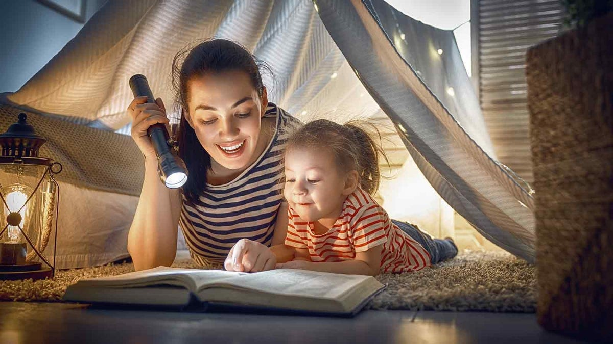 Woman reading to a young child using a flashlight under a sheet fort