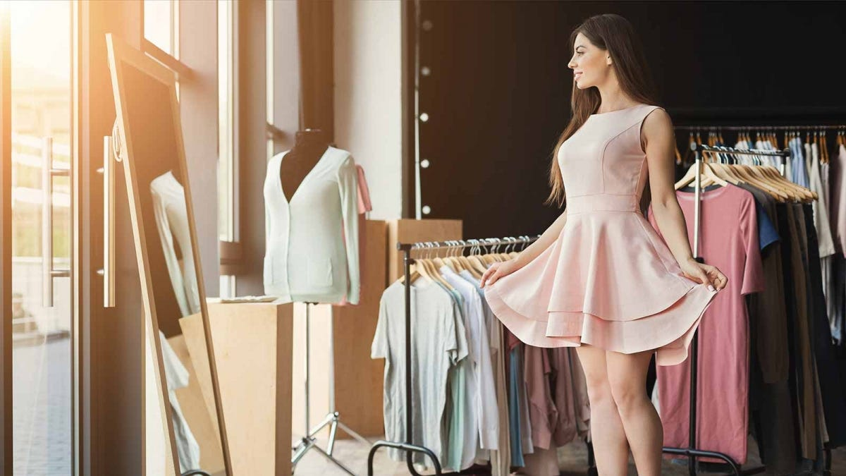 A woman trying on a dress in front of a mirror in a boutique.