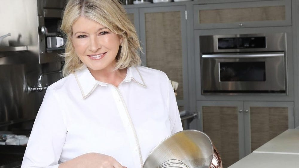 Martha Stewart holds up a whisk and a bowl.