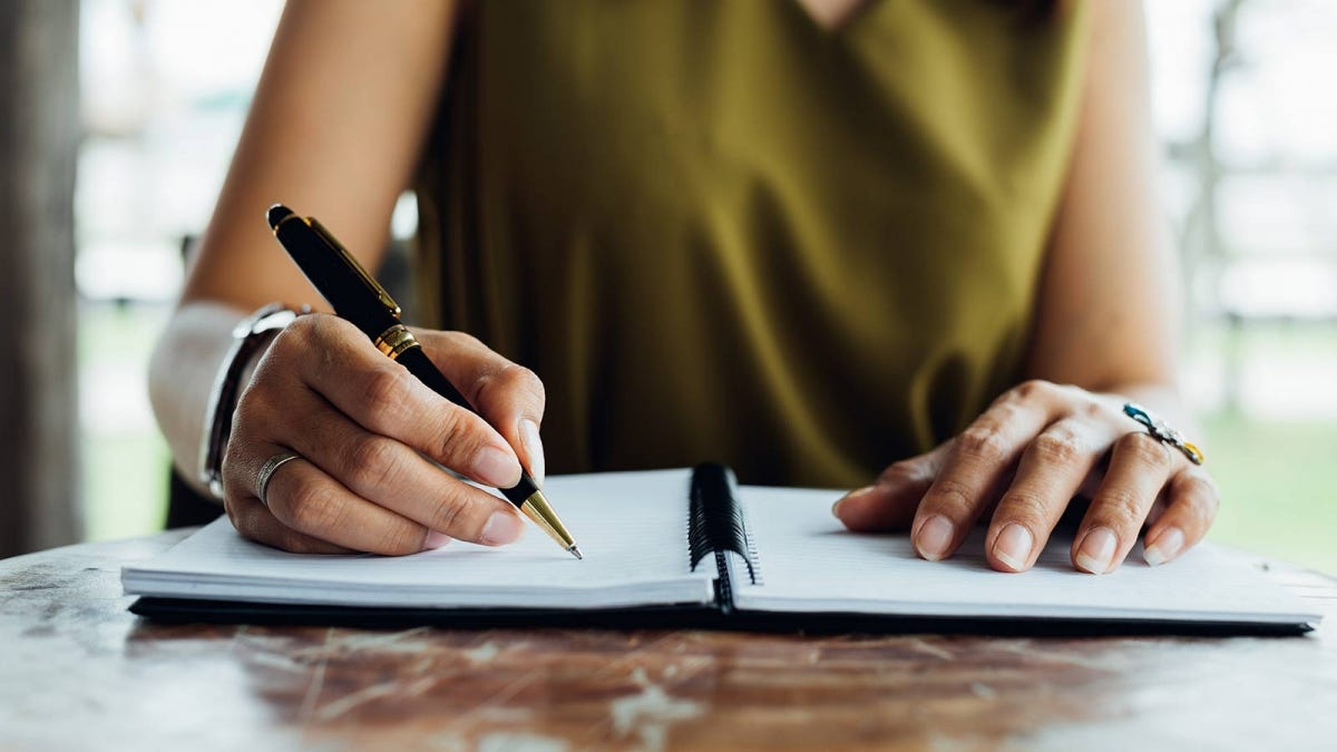 A woman checking off a list in her planning notebook.