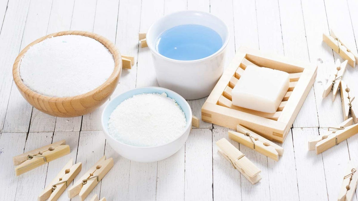 laundry detergent substitutes like a laundry soap bar and baking soda, on a white table