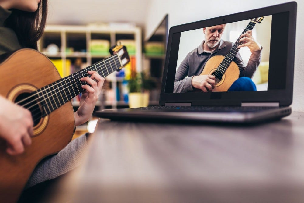 Someone learning to play guitar by watching a video on a laptop.