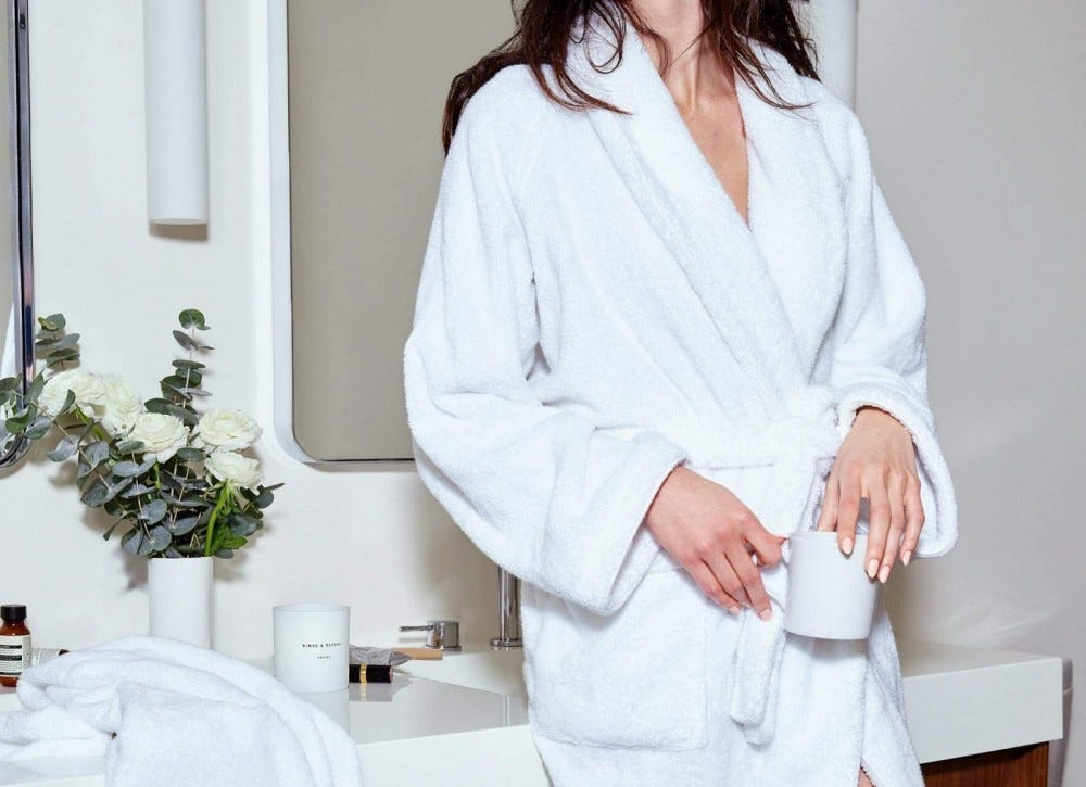 A woman in a bathroom wearing a white Snowe bathrobe.