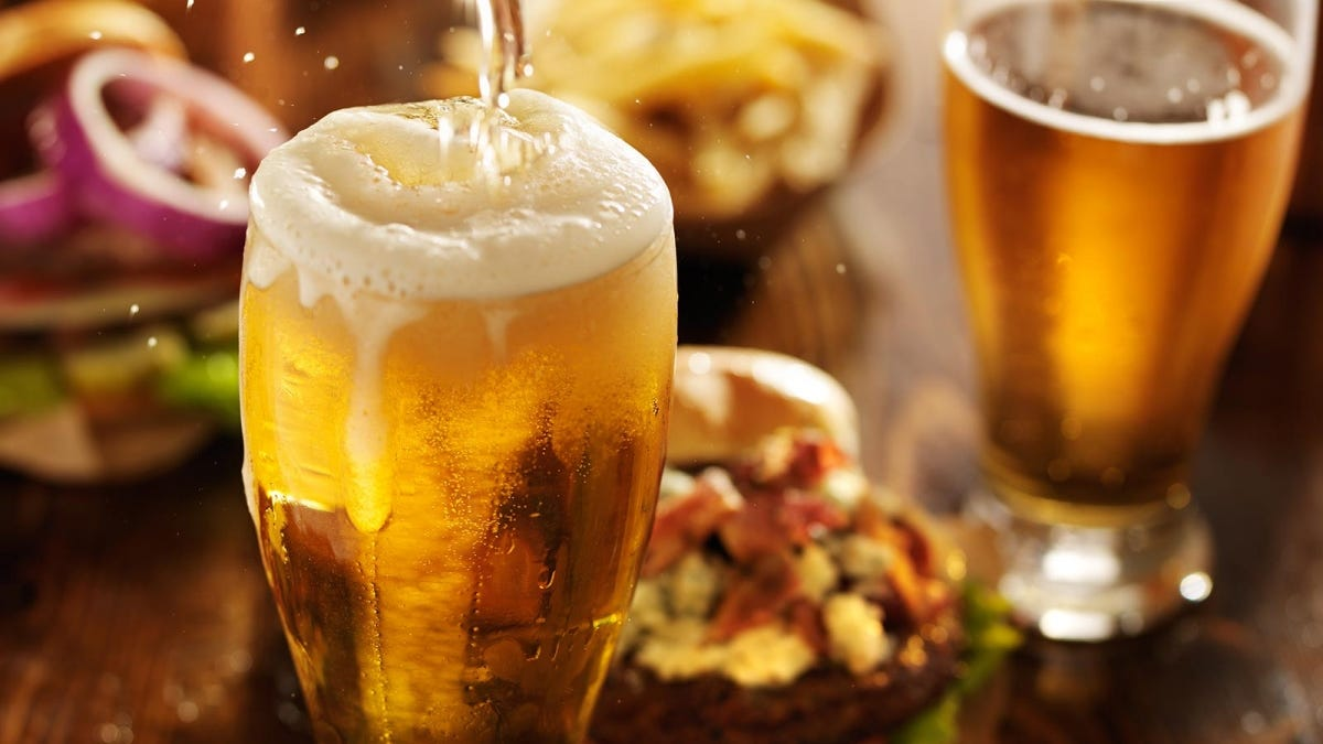 A tall glass of beer sitting in front of a table full of food.