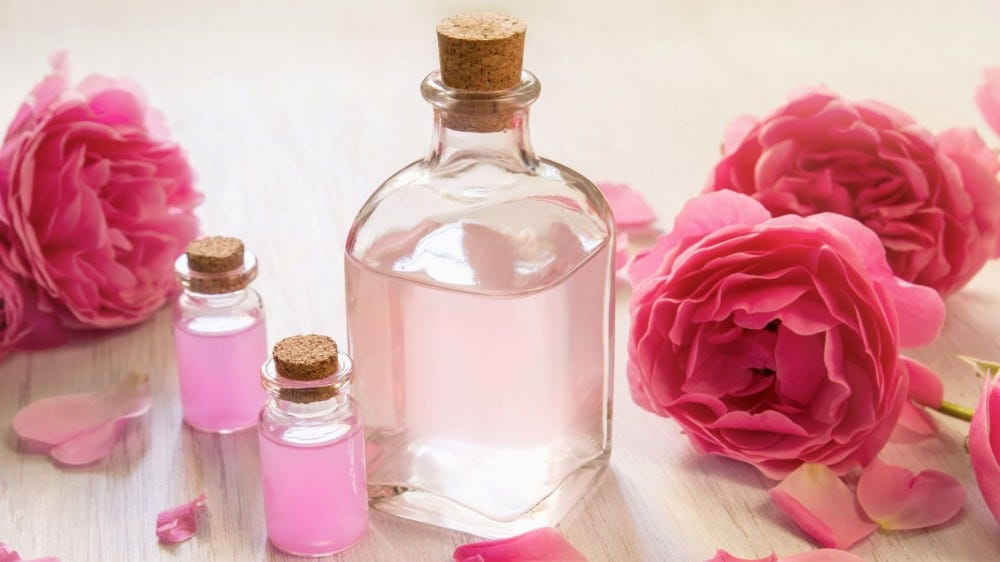 Three bottles of rose water surrounded by pink roses.