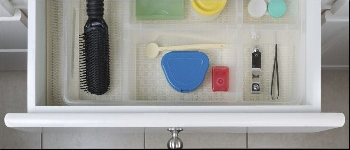 Open bathroom drawer with personal hygiene accessories displayed