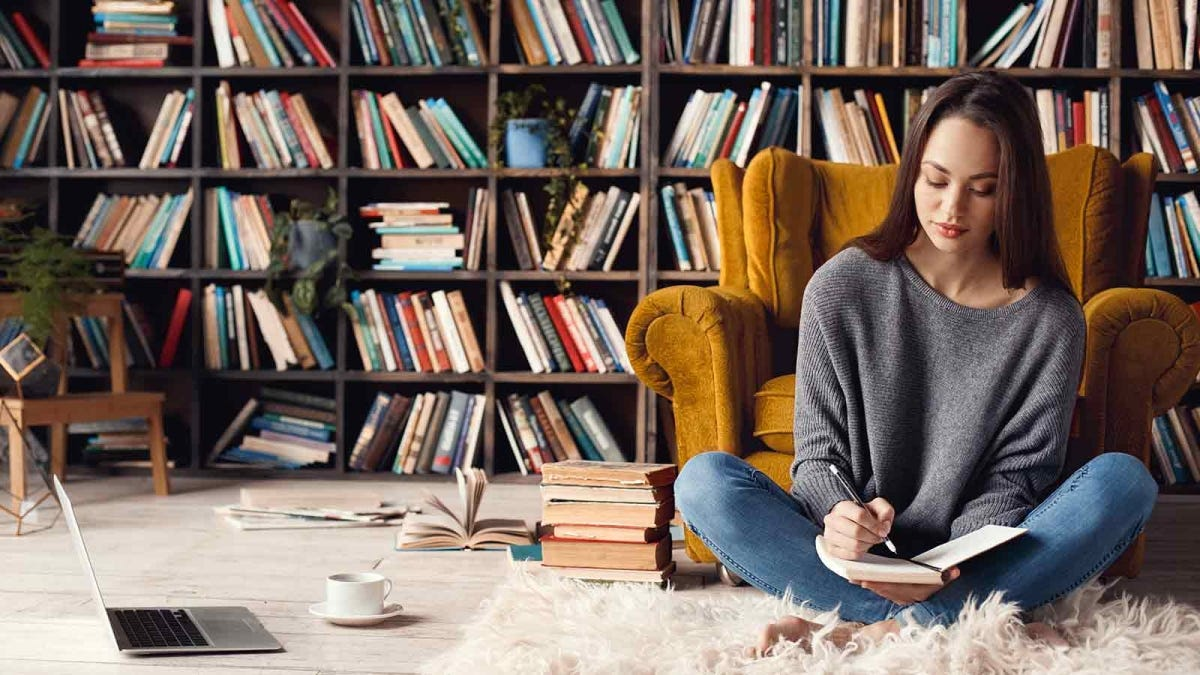 Woman sitting in front of messy bookshelves and writing in a journal.