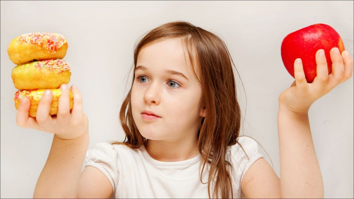 A young girl with food contemplates whether she would prefer healthy apples or unhealthy donuts