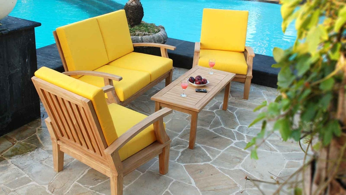 An outdoor furniture set beside an in-ground pool.