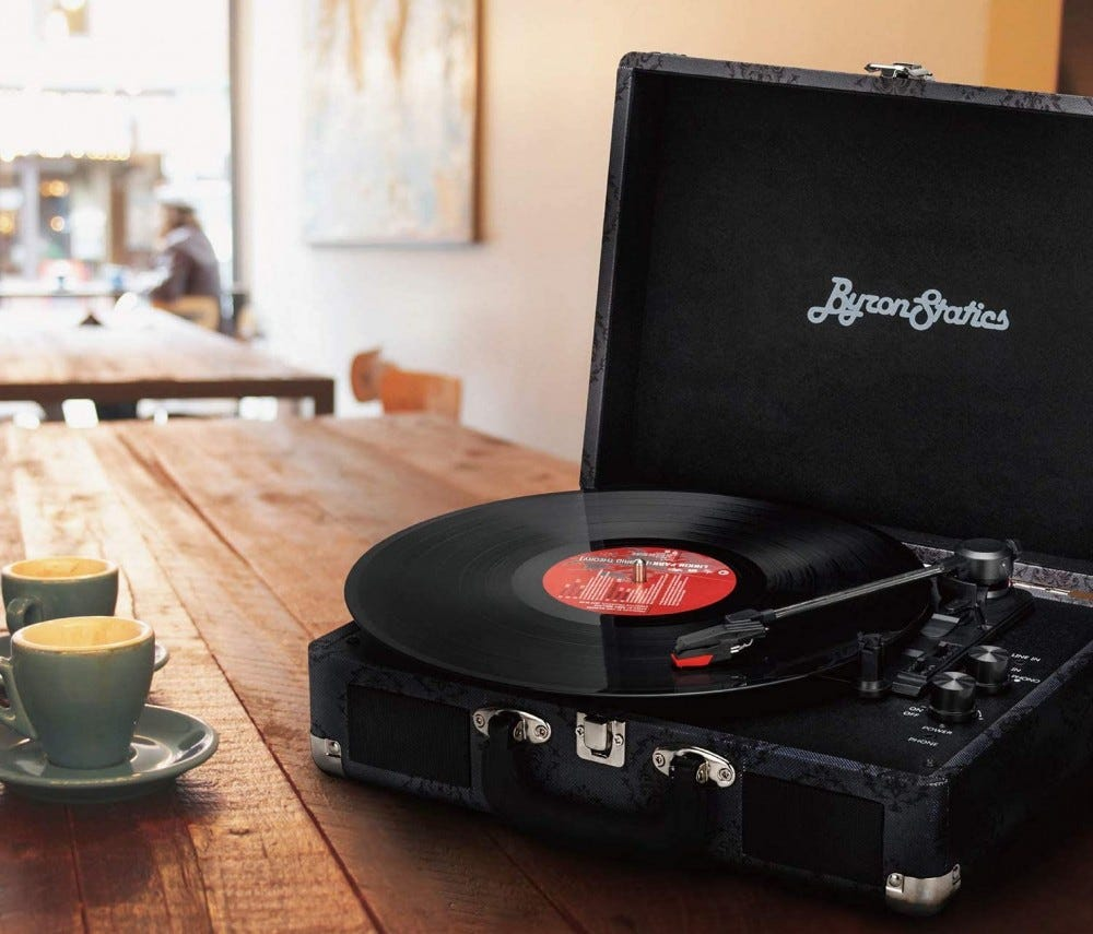 Black record player sitting on a wood table in a cafe